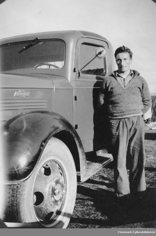 Hans Sandeng fotografert ved siden sin lastebil (Chevrolet 1938 med norskbygd førerhus) i Børselv før krigen. Han var den første som kjørte over brua i Børselv i 1939. Vi ser en liten del av brua i bakgrunnen.