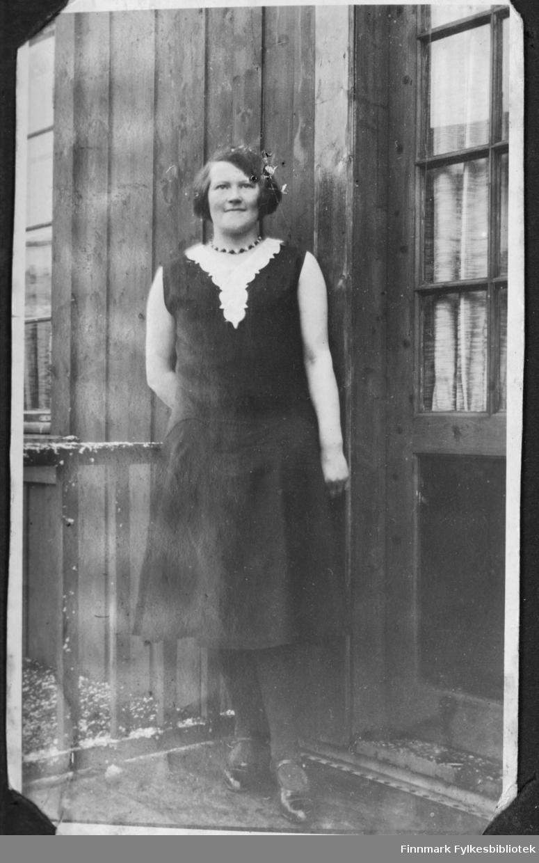 Sofie Andreassen (gift Lindbäck) står på trappa utenfor et hus i Børselv før krigen.