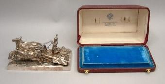 """Statyett i silver av en rysk """"troika"""", dvs ett hästspann med tre hästar som drar en släde. Silverskulpturen förvaras i en röd ask av läder.  Inskription: """"C. Adelsköld ille, Rautatiomuisto Pohjanmaalta, 1877"""", vilket betyder ungefär """"Järnvägsminnesmärke från Österbotten""""."""