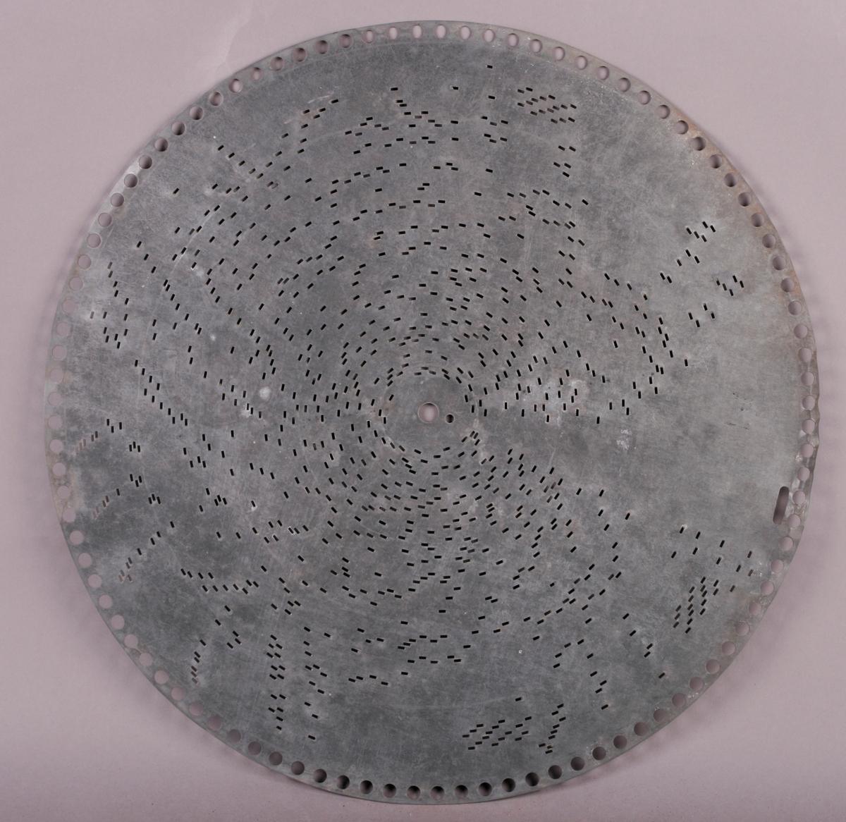 """Perfortert metallplate med pigger på undersiden. Programmert musikk for platespilledåse. 76-spor, Ø 40 cm. Drivsystem: perifere hull langs kant (ø=7 mm) for perifer tannhjulsdrift, samt et 19 mm avlangt hullfor å markere slutt/stopp.  Sentrumhull, diameter: 8 mm, samt et """"satelitt-hull"""" ved siden (ø=4 mm) på RMT 932 M-Ø, AB,  AD-AF, AH-AM, AP-AT (31 stykk). U-formet pigger på underside av platene."""