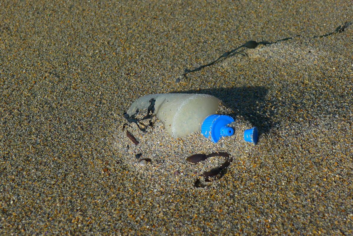 Brun sandstrand der det stikker opp en gammel spenolflaske av sanden. (Foto/Photo)