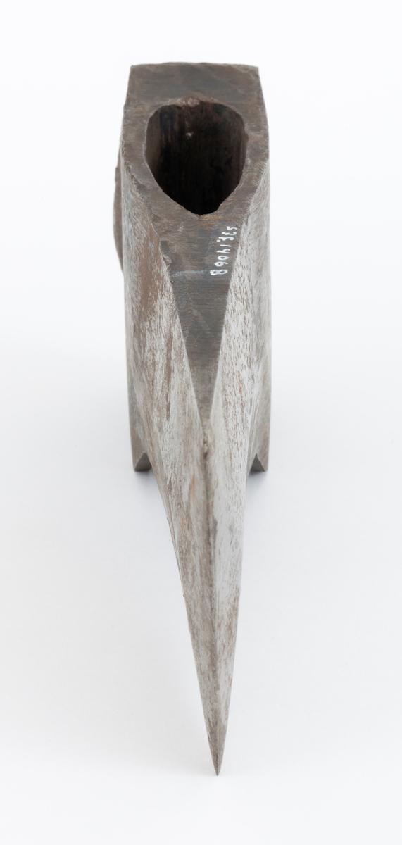 Uskjeftet øks, produsert av den svenske produsenten Hults Bruk i Östergötland. Øksehodet er 20,9 centimeter høyt. Den nederste delen av øksebladet er 8,0 centimeter bred, målt i rett linje mellom den konvekst buete eggens ytterender. Bladet er grovest langs midtaksen, bare den nederste delen mot eggen er planslipt. Den fremre tverrenden er en aning konkav, men nesten rett. Den bakre tverrenden skrår innover mot buksida av «øyet» (skafthullet). Kjakene er forlenget med slakt buete fliker på denne sida. Slagflata på nakkesida er 7,3 centimeter lang og 3,9 centimeter bred. De siste par millimeteren av dette breddemålet må nok tilskrives deformasjoner som er oppstått fordi øksenakken har vært hyppig brukt som slagredskapet. Godset i denne delen (mellom den øvre delen av «øyet» og den nevnte slagflata) er cirka 2,5 centimeter tjukt. Øksehodet kan sde ut til å ha vært innsatt med en mørk lakk, men mesteparten av lakken er vekkslitt. Den nederste delen av bladet har antakelig alltid vært stålblank. Øverst på høyre side av øksenakken finner vi produsentens runde stempel med forbokstaven «H».