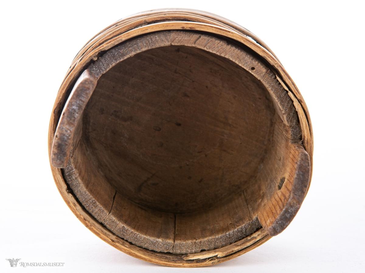 Liten, lagget ambar med ører, uten lokk. Tett i tett omslått med trebånd og gjorder i hele høyden.
