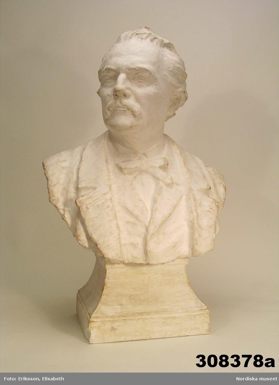 """Huvudliggaren: """"a-c, Byst, 3, st, skulptur, gips; porträtt av Artur Hazelius; klädd i kavaj, väst, kravatt; huvudet vänt åt höger; skador se bilaga. Br 46 cm. [Tillv.] J. A. Wetterlund (1858-1927], 1903; funnen omärkt på vinden. G. 15/9 1981 [av] Okänd."""""""
