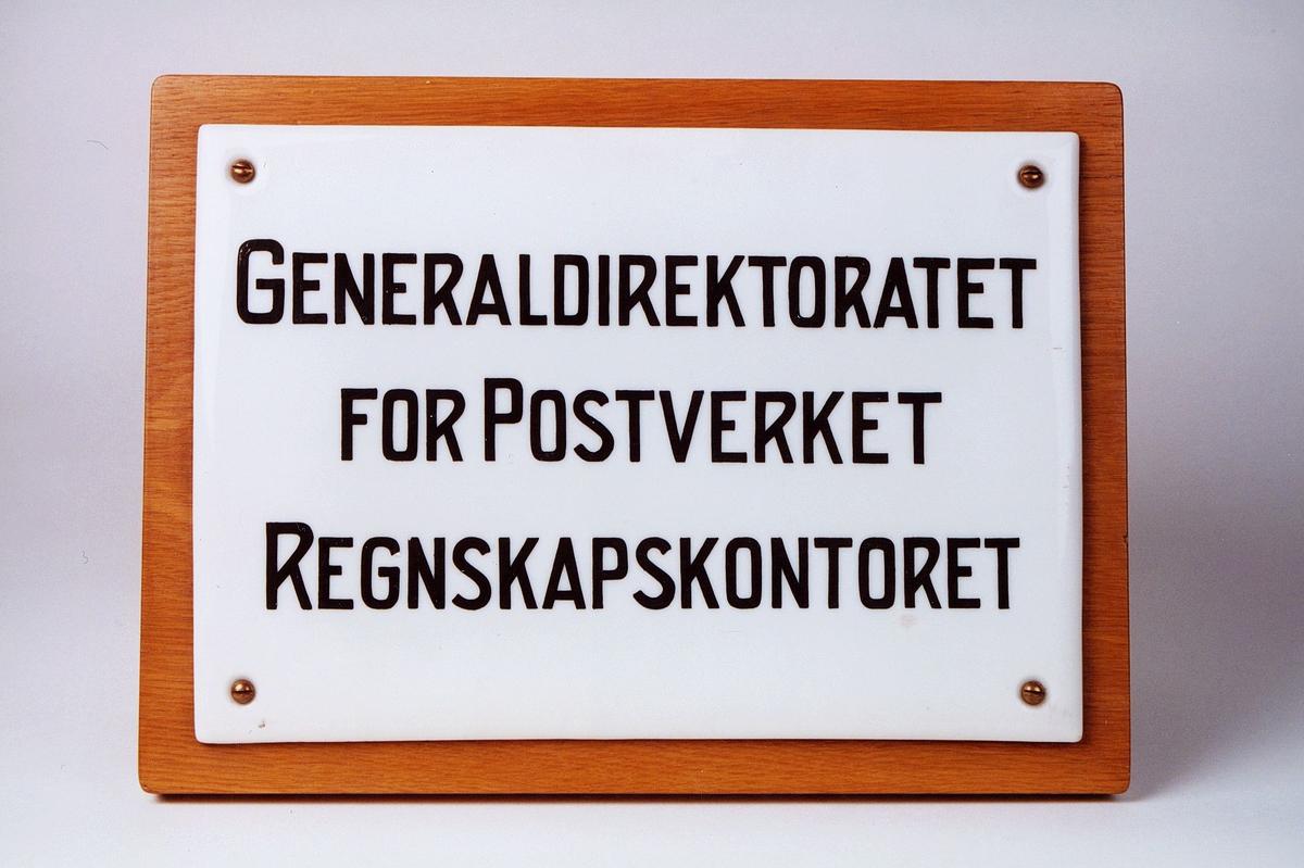 Skiltet er påsatt treplate. Skiltet har sort skrift. Det er brukt i Poststyret. Generaldirektoratet for postverket, regnskapskontoret.