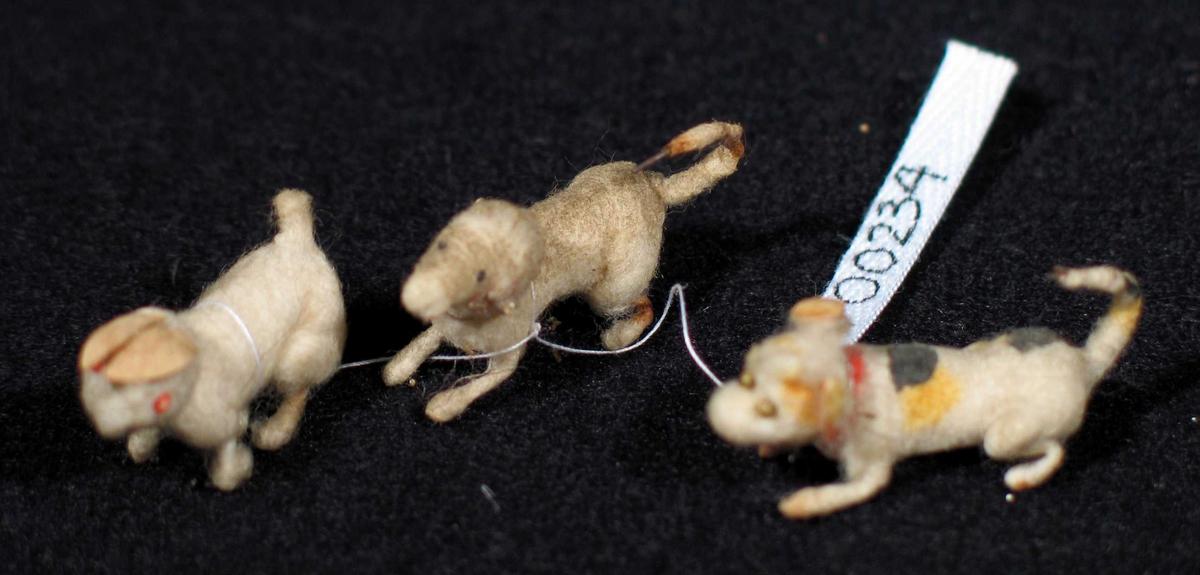 Små dyr laget av metalltråd surret med vatt og malt. Ørene er laget av papp. Det er to hunder og en kanin.