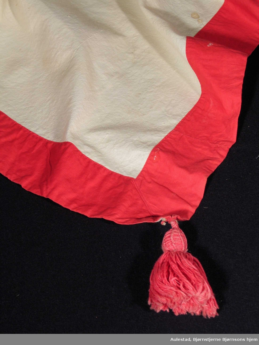 Hvit stor duk med påsydd rød kant og dusker i hvert hjørne. Rødt monogram brodert i midten.