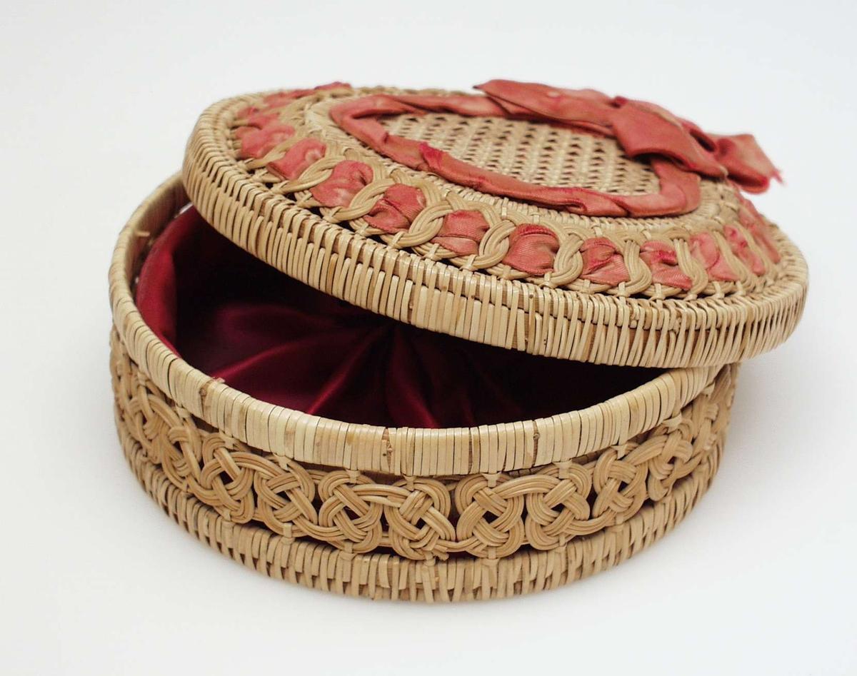 Flettet kurv med lokk med opphøyd kant og silkebånd. Kurven har snodd kantmønster. Den er trukket med silkefor.