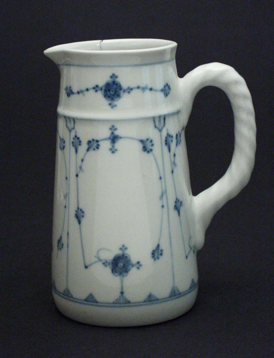 Hvit mugge i porselen med blått stråmønster. Hanken har riller i godset.