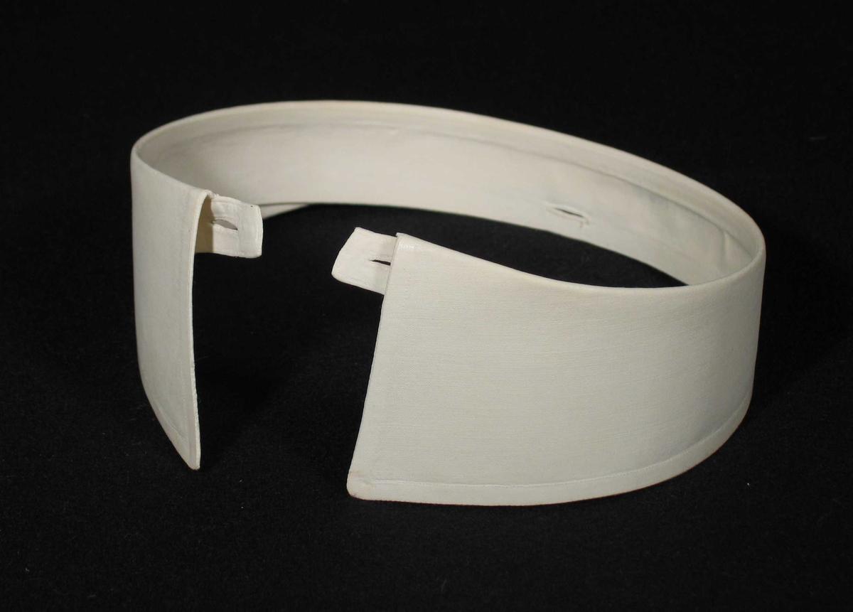 Stivet hvit snipp i toskaft bomullsstoff. Et knapphull på hver side og et midt bak. Merket med navneblekk i nakken.