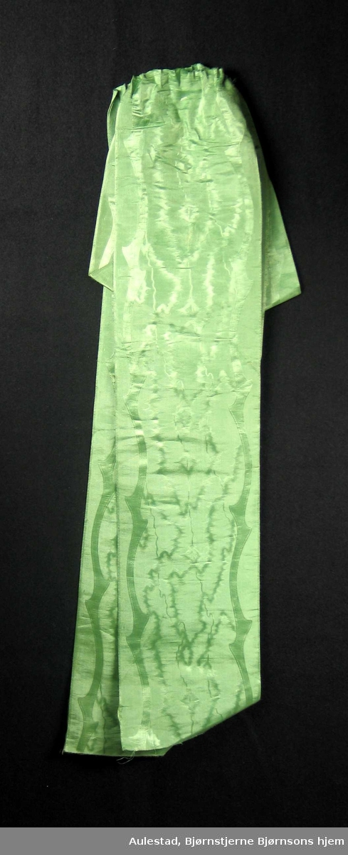 Begravelsessløyfe i grønn silke med innvevd mønster. Tekstdelen er borte.