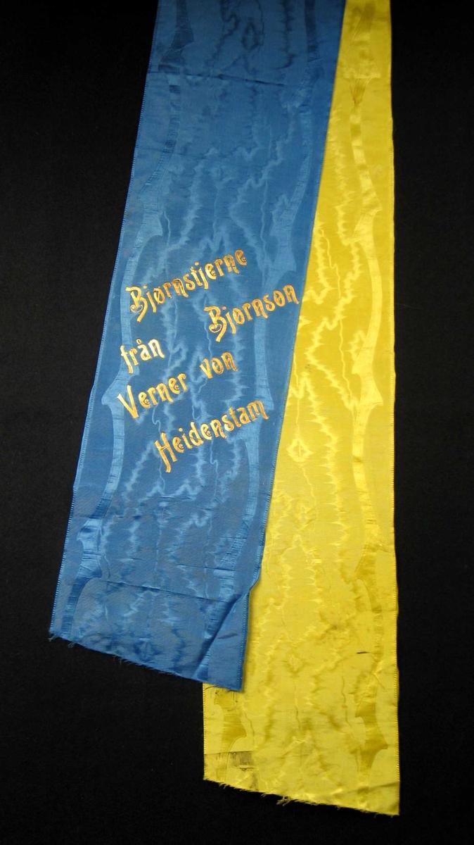 Begravelsessløyfe i blå og gul mønstret silke.