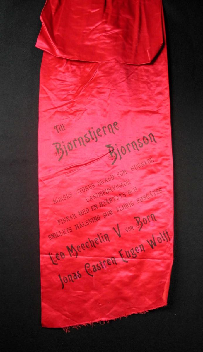 Begravelsessløyfe i rød silke med svart tekst.