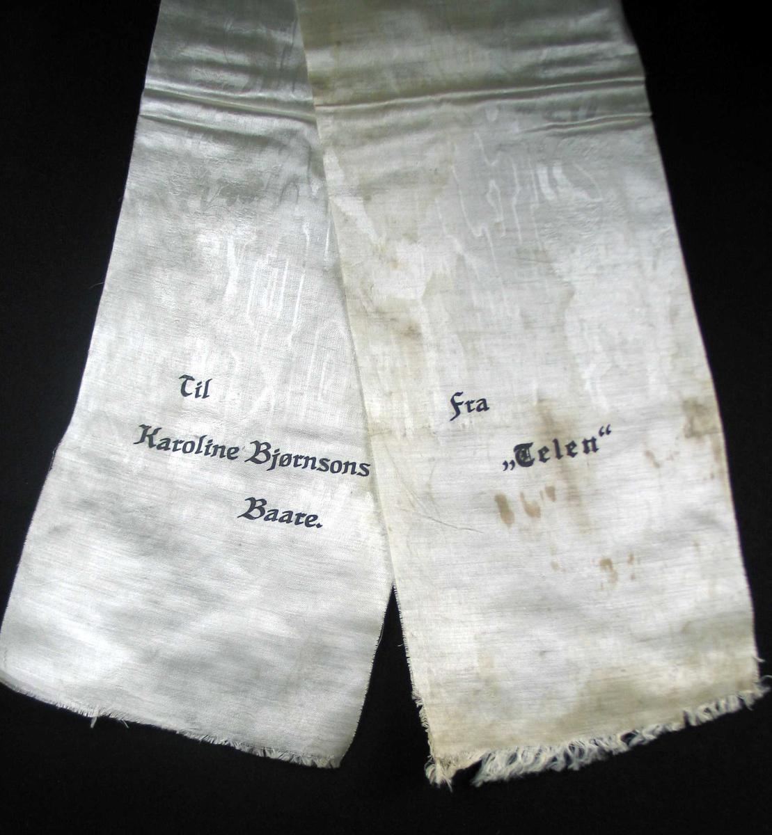 Begravelsessløyfe i hvit silke med svart tekst.