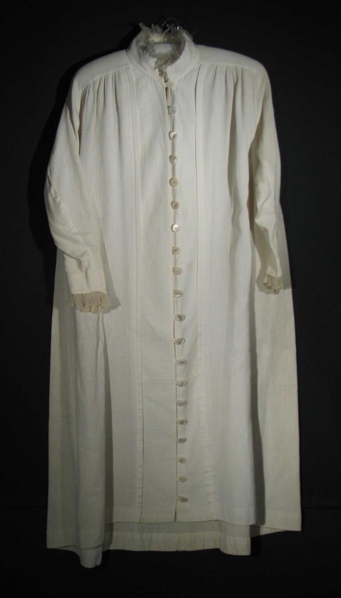 Lang hvit frontknappet kjole i bomullspicquet med stripet struktur. Kjolen har 20 perlemorknapper som lukkes med hempe. To skrådde sømmer/kiler under hvert erme. Skulderstykket av tøy på tvers. Forstykket er rynket inn i skulderstykket. Kjolen er åpen fra halsen og ned. 10 cm bredt, tverrstripete parti sydd til forstykket med en mot midten brettet 1,5 cm dyp fold danner frontpartiet. 4,5 cm belegg i oppbrett nederst. Stående linning, 46x6cm, av dobbelt tøy, kantet med slitt silkerysj. Smalt to-søms erme med høy topp og buet linje ned over håndbaken, belagt og kantet med 3 cm bred, dobbeltlagt rynket tyll/bobinette. Alle belegg og skonninger av to-skafts bomullstøy.