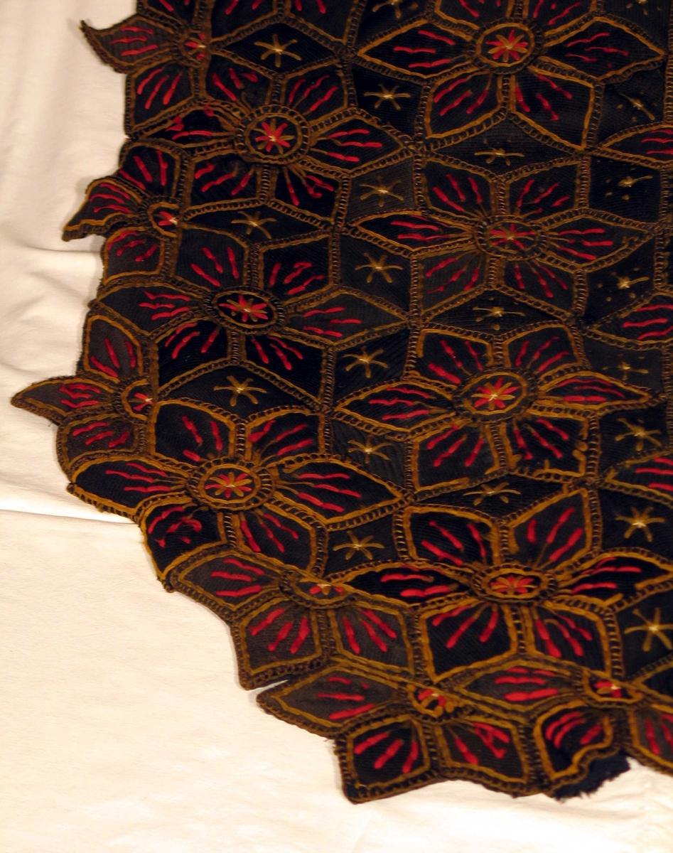 Tøybiter er alle i dobbeltvev, med brede og smale pikéstriper. Vrange enten i flosset bomull eller filtet ull. To hovedformer går igjen på lappene: snippform 7-8cm x 4 cm og rundinger 4,5 cm. Alle lappene er kantet med grønne knapphullsting med en rad lange kjedesting innenfor. Midt i snippene tre røde striper, kjedesting. Midt i rundingen en stjerne av fire røde og fire grønne kjedesting. Hovedmønsteret er en seksbladet rose med en runding i midten. Rosebladene støter til hverandre. De naturlig snippformede åpningene i mønsteret er fylte med ukantede, underliggende snipper. Alle med olivengul eller grønn stjerne av seks kjedesting og et lite beige kryss i midten. Teppet er ovalt og forsynt med halve, dvs trebladsroser langs kantene. Teppet er fôret med flere slag, delvis falmet og fillete svart og gråsvart fôrstoff av bomull. Tre opphengshemper av tvinnet snor på ene langsiden.