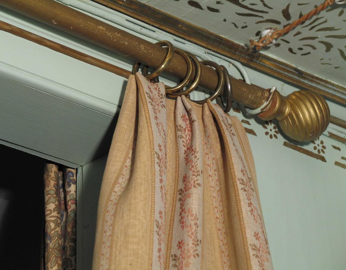 To lengder portierer med langssgående blomsterborder. 11 cm bred gul stripe i moirert rips, småmønstrete midtbord. 5 cm bred stripe i lin med bølgete blomsterranke. En mønsterrapport i bredden: 16 cm. Fôret med seks-skaftet kypert i gul bomull. Bunnfargen er beige med dekor i gult, rosa og grønt. Langs kanten mot døråpning og nederst påsydd vevd bomullsbånd med ullponponger, festet i uttrukket ullinnslag. Øverste kant foldelagt og isydd fem messingringer.