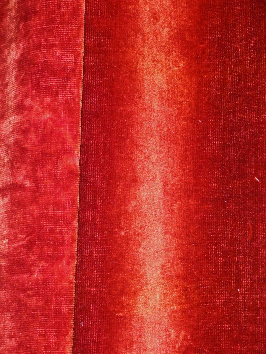 Rødbrun portiere i bomullsplysj foret med grønn sateng.(Opprinnelig svart?). Isydd metallringer, samtidig som det er lagt en liten fold. Hengt på kroker i en trelist. Tatt tilside med metall-lenke. I enden en trekule med knotter.