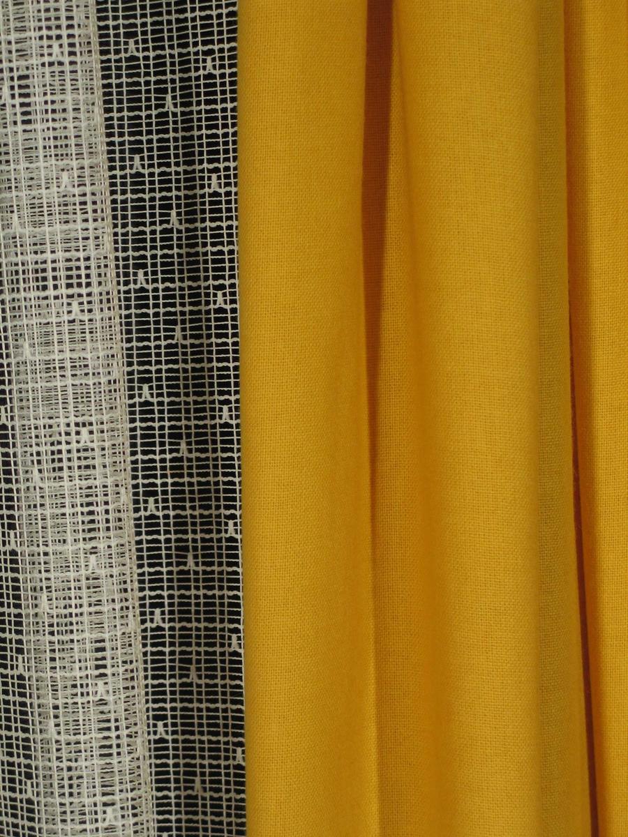 Et fag gule gardiner i to-skaft ullstoff.