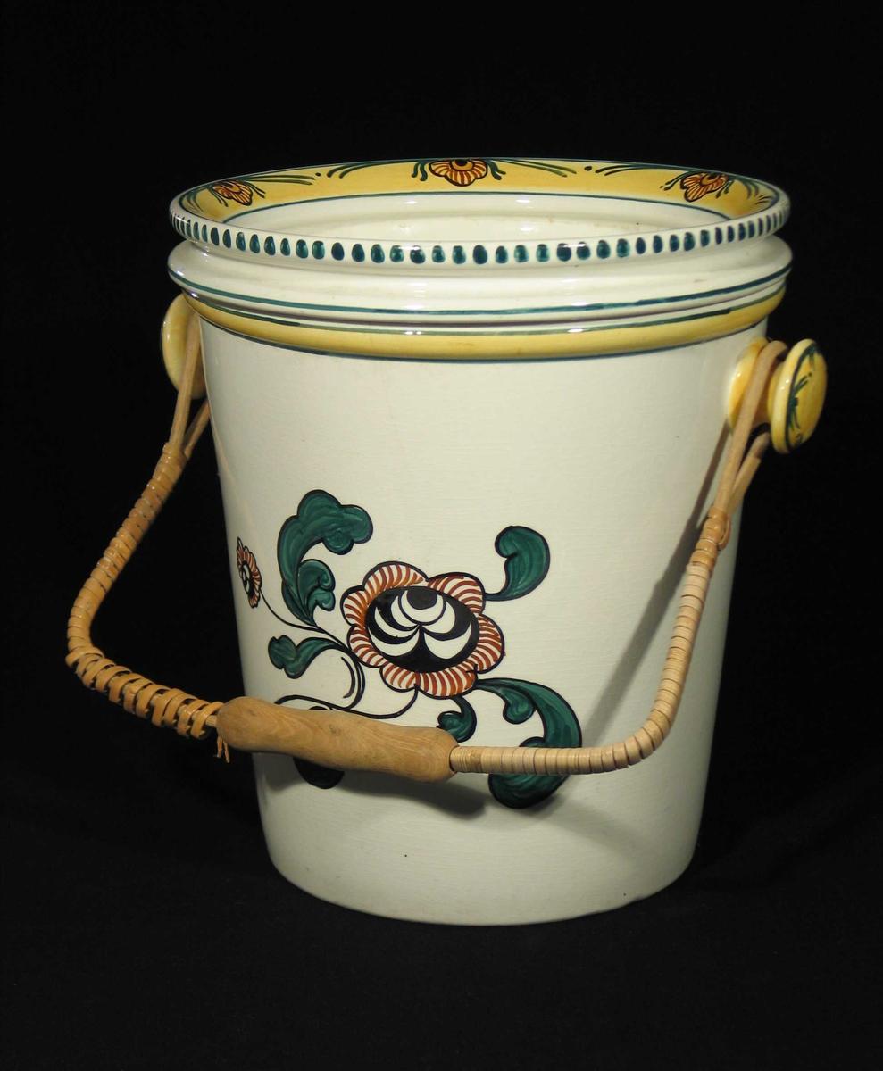 Hvit toalettbøtte med lokk og kurvhank. Bøtten har polykrom dekor i form av blomster og bladverk. Lokket har gul kant og blomsterdekor, ytterst en grønn stripe og grønne dobber. Hankeholderne er gule med grønn dekor.