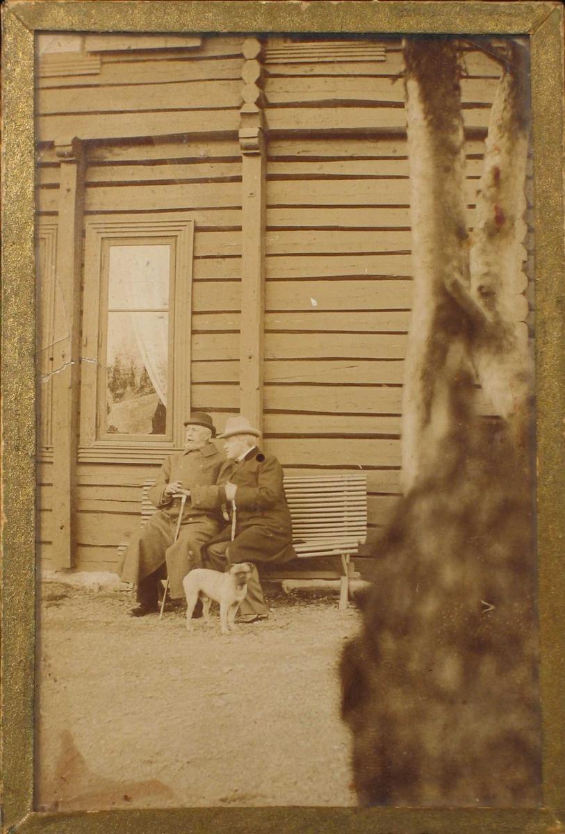 To menn på en benk foran en tømmerbygning. En hund ved siden av.
