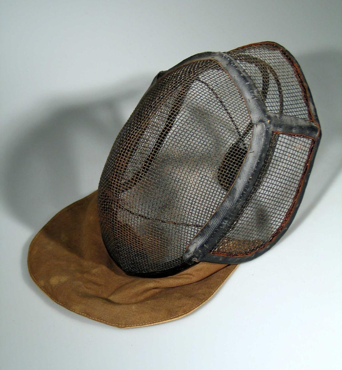 Fektemaske laget av metallgitter med bøyle bak og tettvevet dobbelt stoff foran for å beskytte halsen.