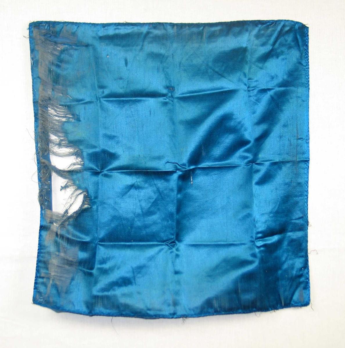 Avsprettet bakstykke av pute. Det er blå natursilke.