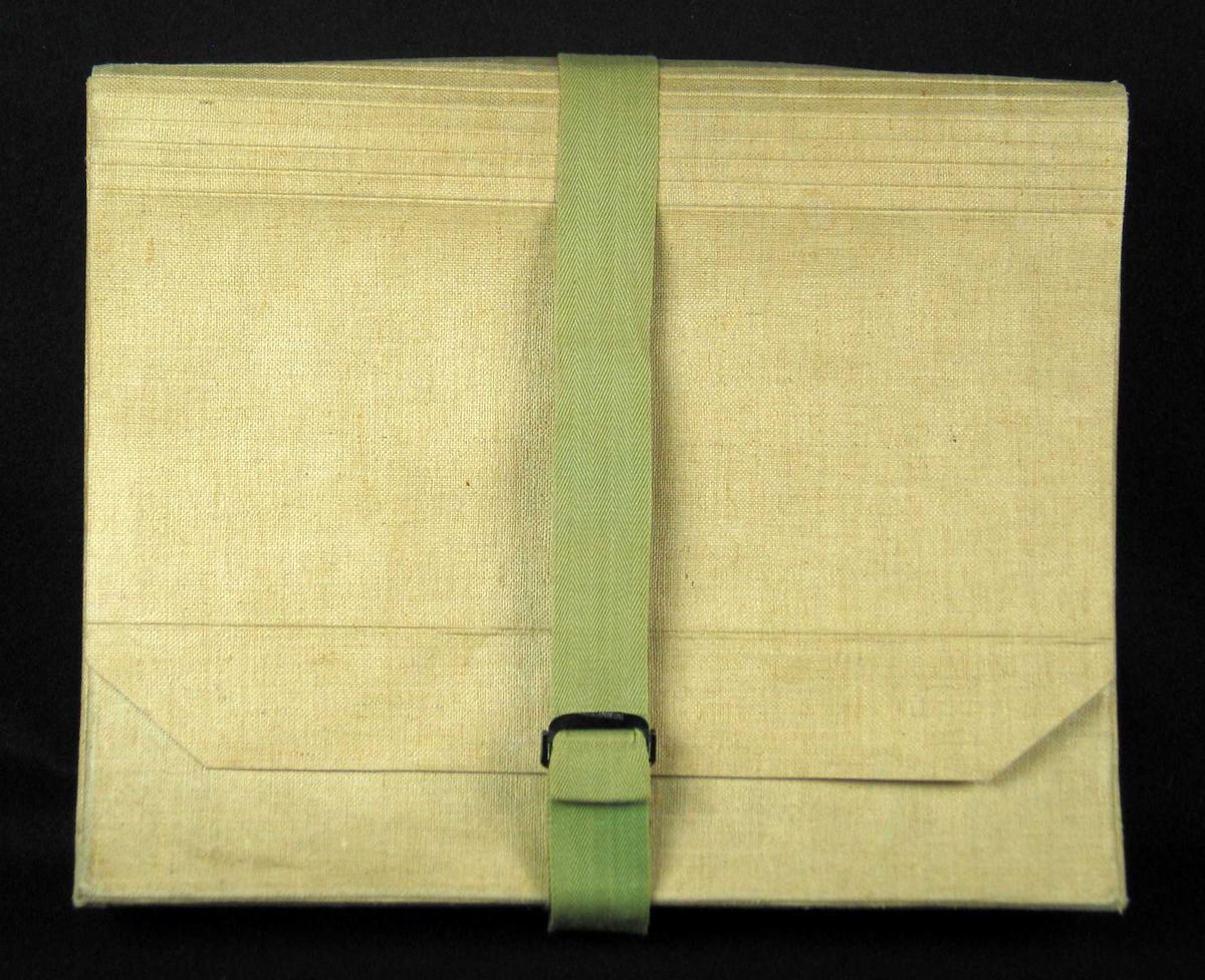 Grå arkivmappe i kartong trukket med kanvas. Grønt bånd med svart spenne.