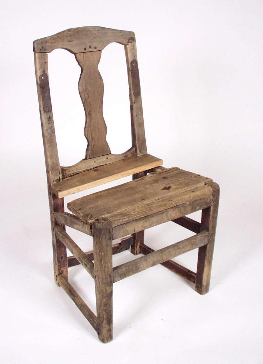 Enkel trestol. Har vært rødmalt, men fargen er svært avslitt. Rester finnes bak på ryggen. Stolen har blitt reparert med spiker og metallstykker i senere tid.