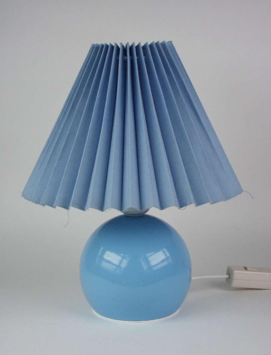 Blå lampe med rund sokkel og plissert skjerm.