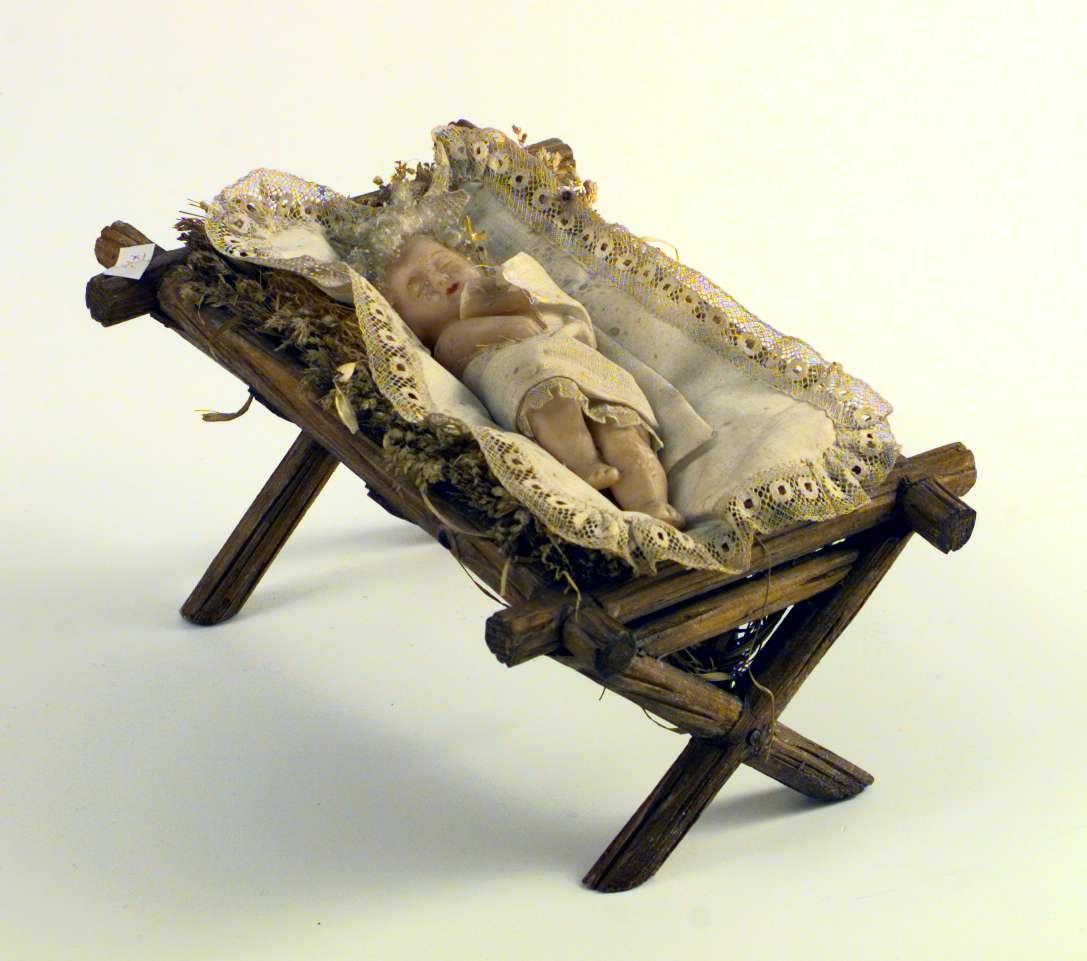 Julekrybbe laget av tre og fyllt med strå og treull. Jesusbarnet er laget av voks og har saueull til hår. Han er svøpt i et bomullsklede med blondekant, og han ligger på et teppe av bomull kantet med blonder.