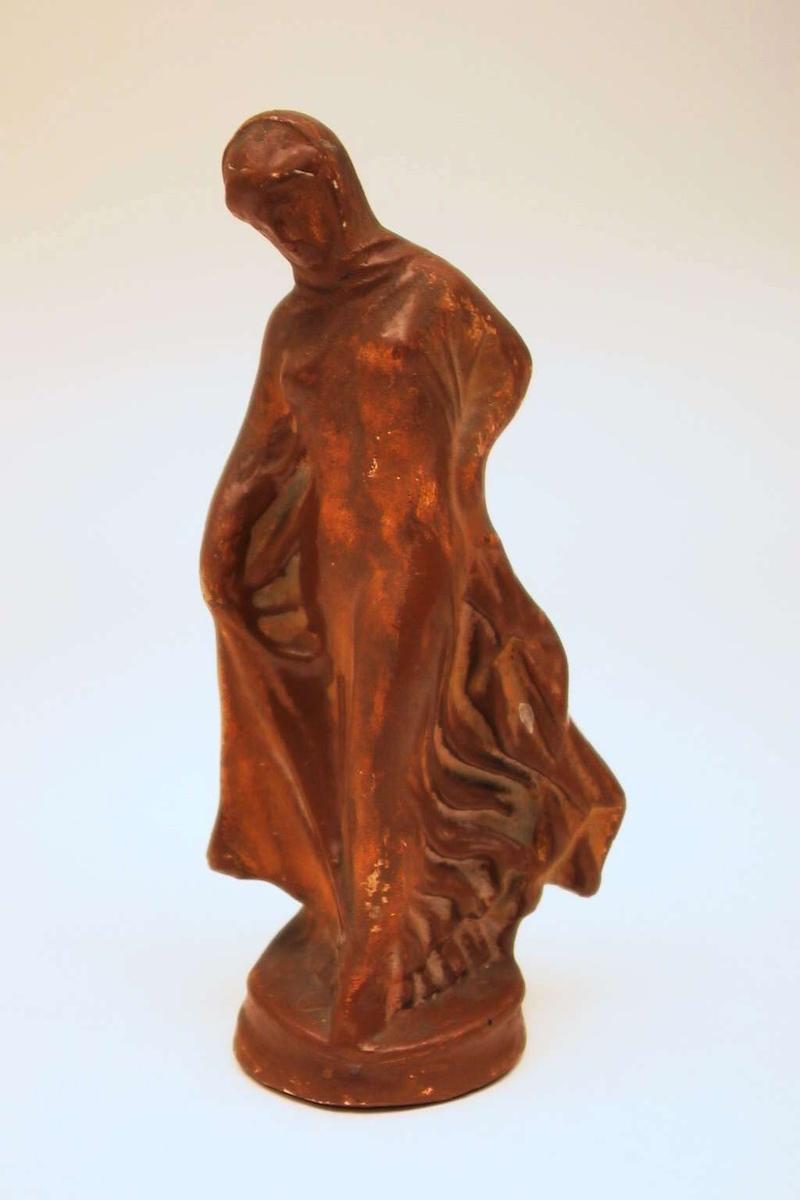 En stående kvinnefigur støpt i gips. Figuren er malt brun.