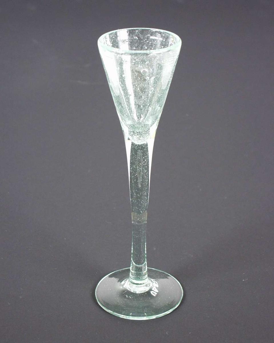 Brennevinsglass, spissglass, med høy stett. Glasset er svakt grønt.
