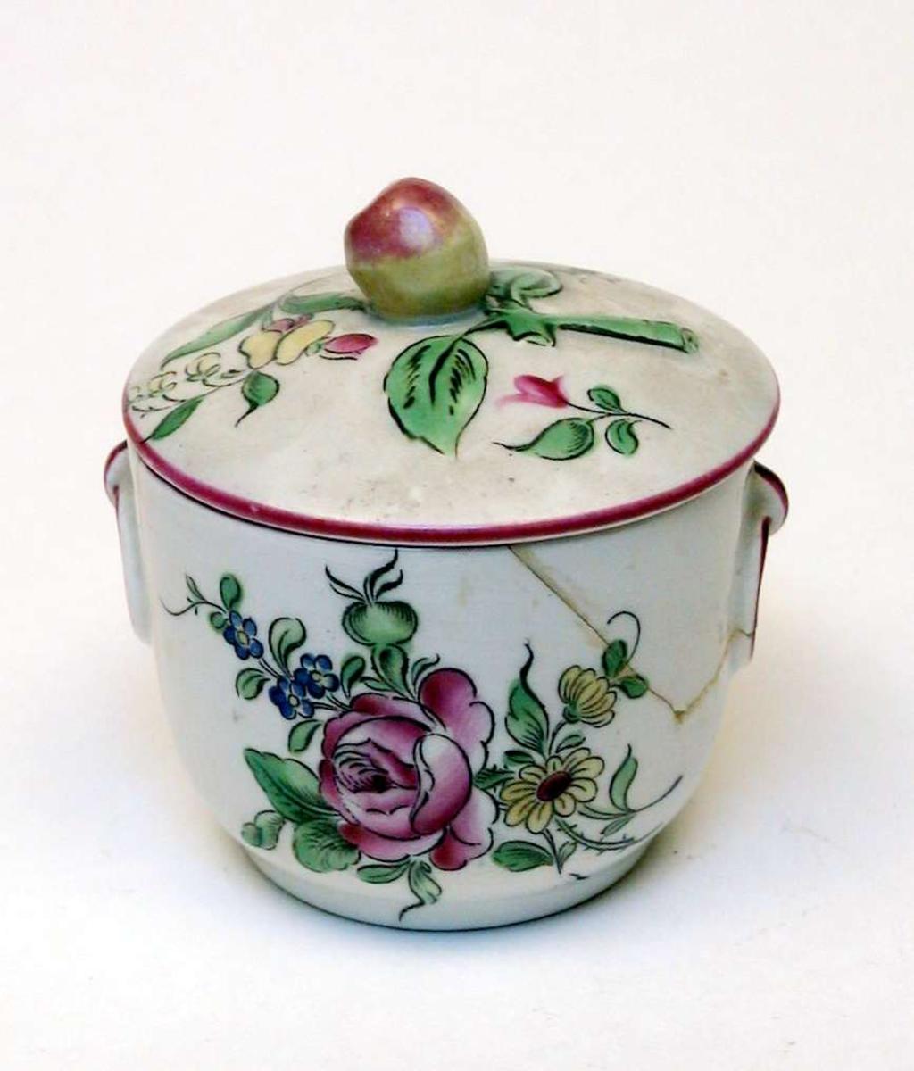 Liten krukke med lokk i kremfarget keramikk og med blomsterdekor. Den er stemplet Demi-porcelaine, Luneville, France, med bokstavene K og G rundt en krone. Krukken er limt.