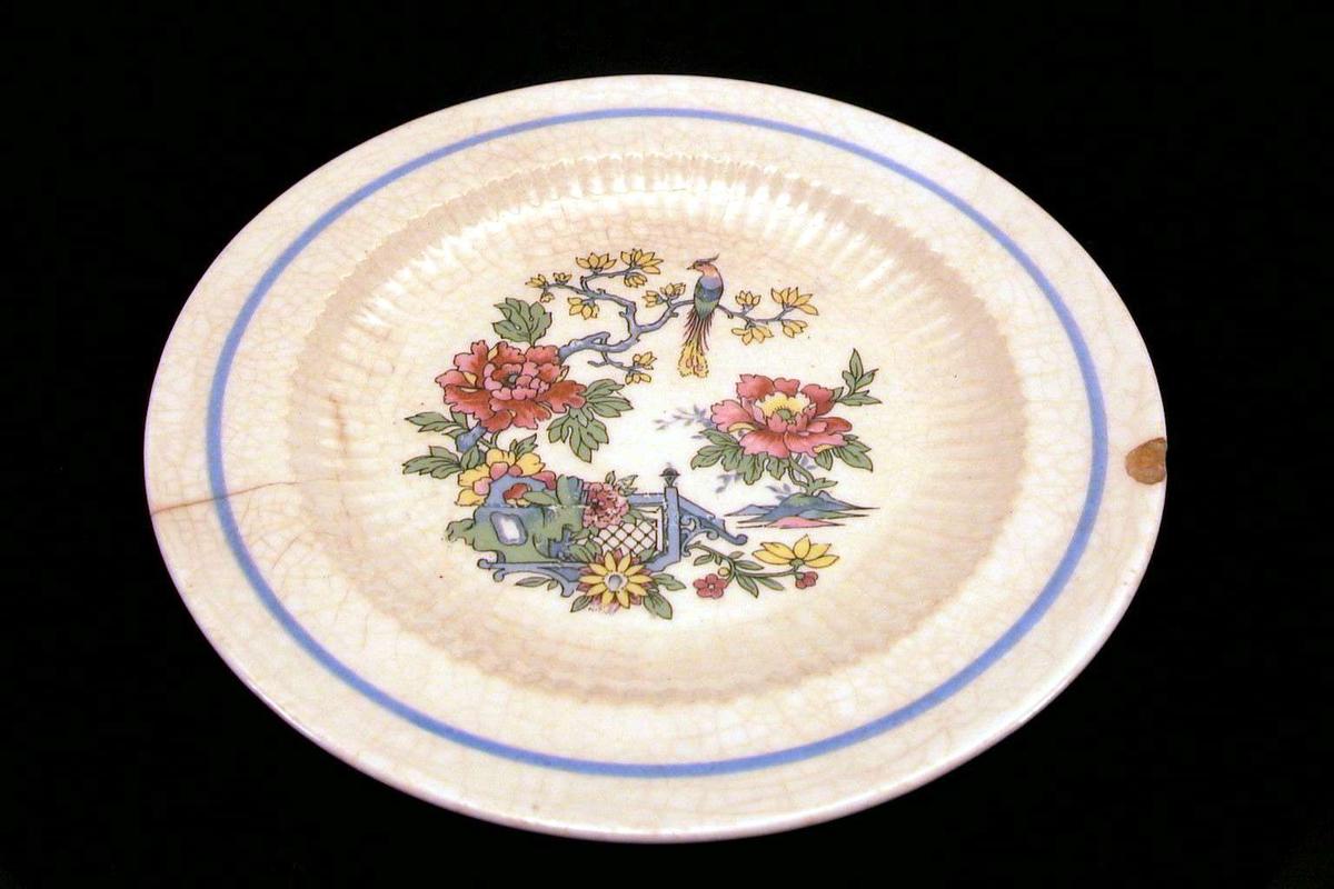 Asjett med hvit glasur og østen-inspirert dekor i blått, rødt, gult, grønt. Asjetten er sprukket og der er skår i kanten. Glasuren er krakelert.