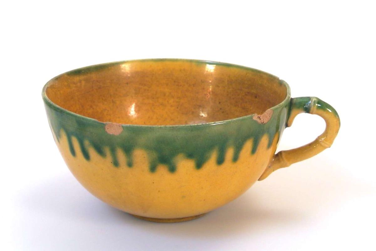 Kopp i gul keramikk med grønn dekor. Brukskunst.