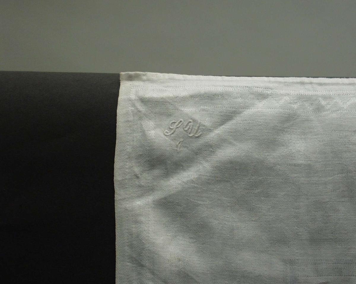 Håndkle i maskinvevet lindamask  med vinblad og med vinranker som ramme. Brodert monogram SU 1. Håndfallete kanter og jarekanter. Påsydde hemper, den ene er fillete. Håndkleet er stoppet flere steder og det er hullete (tynnslitt).
