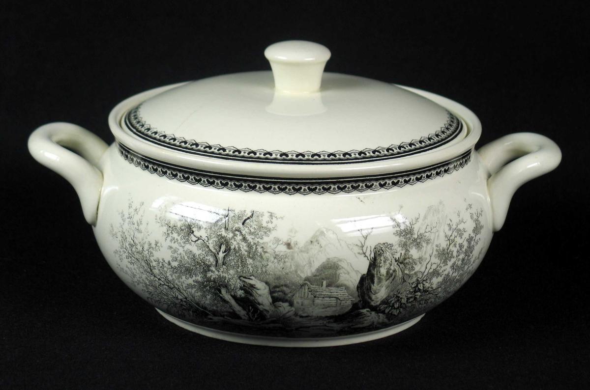 Terrin med lokk i benhvit keramikk med sort dekor. Terrinen har to hanker