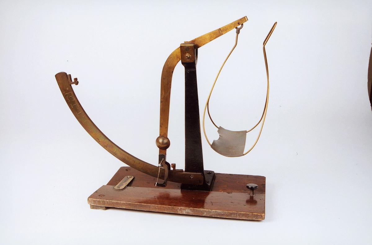 """Pendel/skålvekt i metall montert på trefot . Messingskilt: """"Ulovlig ved kjøp og salg"""""""