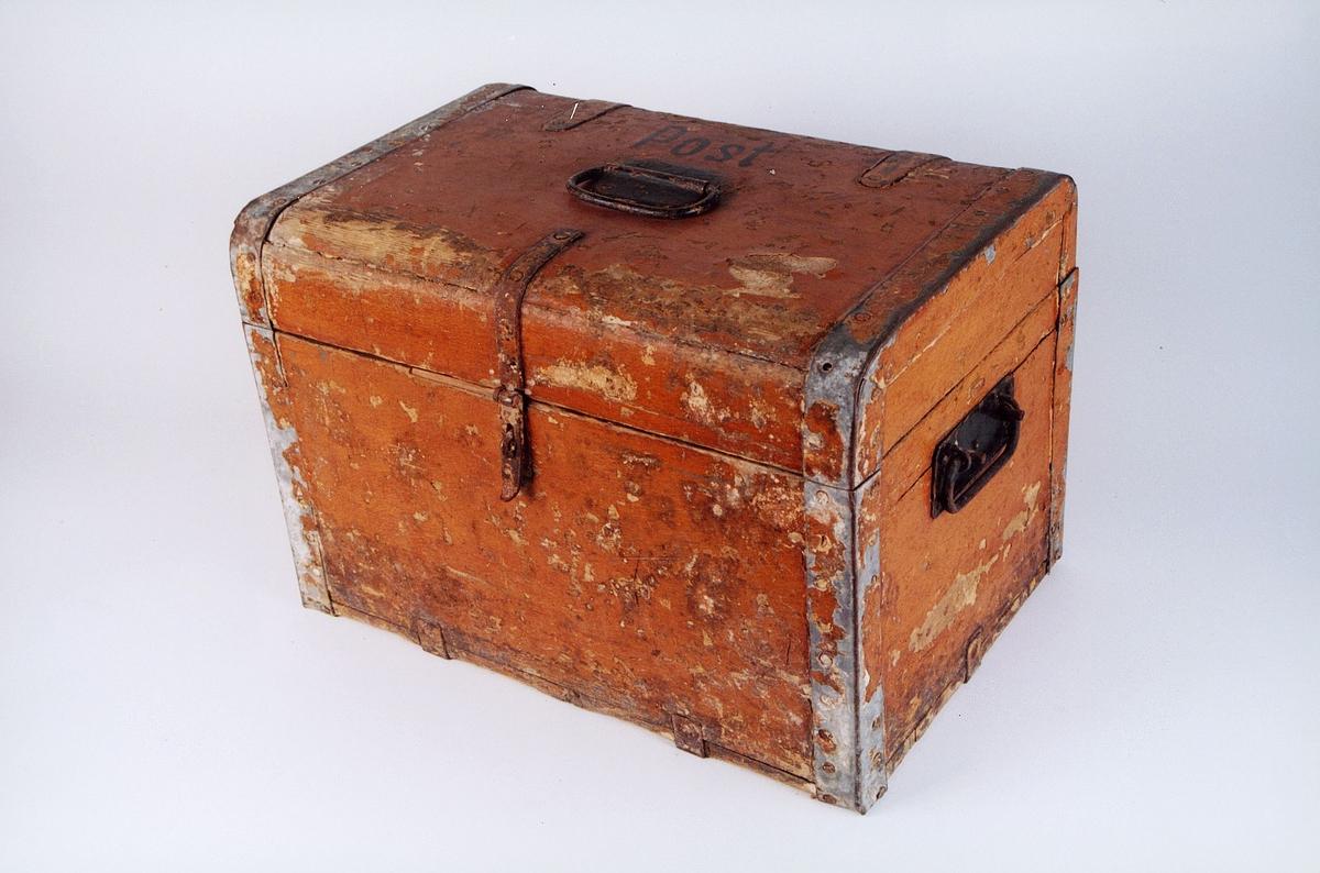 Transportkiste i treverk med jernbeslag og bærehåndtak i jern på lokk og i endene. Låsbar. Påmalt ordet POST