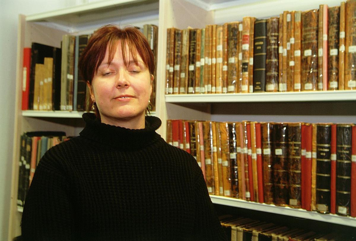 postmuseet, Kirkegata 20, biblioteket, Elin Eskerud står foran bokhyller med Sirkulære, nærbilde