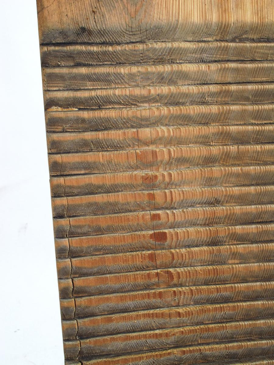 Vaskebrett,  begynnelsen av 1900 årene. Furu.  Avlang plate, avrundet i hjørnene,  ca. 20 cm. stykke glatt tre øverst med et hull for opp  hengning. De to nedre tredjedeler riflet med kl,  riller på tvers. Baksiden oppskåret med kniv,  sortflekket.  Tilstand: Slitt på vaskesiden, en del slitasjesprekker på  baksiden,  ellers bra.