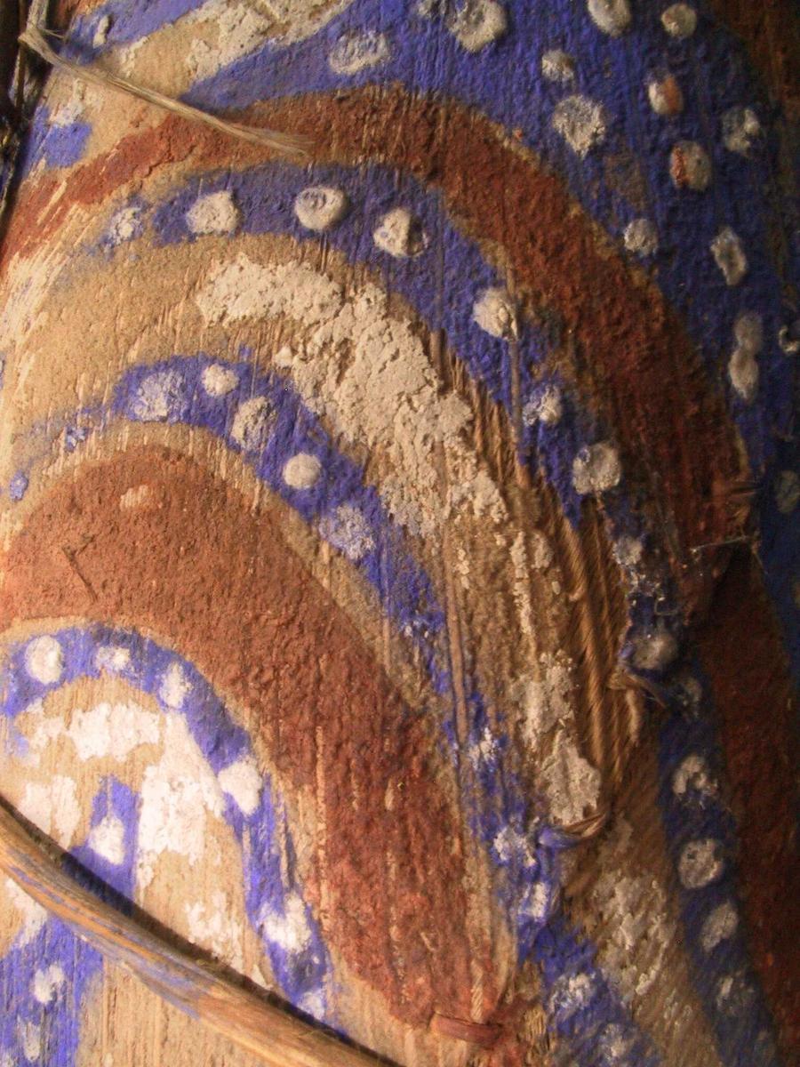 """Malt   bark,   tre  spiler,   hamp,   bast  frynser.  Konisk skjelett av spiler trukket med bark, som er malt med  sterkt blått, terracotta og hvitt i tørre farger (smitter av som  limfarger).  På den ene side plastiske ovale """"øyne"""", smalrygget bred nese  med en  lang hvitmalt trepinn, spiss i begge ender, gjennom  nesevingen. To  flagrende blå """"ører"""" øverst under den store kule formede  hampehode,  mørkebrunt, kortklippet, småkrøllet. Nederst en vidje  ring med to lange bastdusker.  Tilstand 29. 6. 1966: den ene bastdusken sortflekket, en del  markhull sees inni skjelettet, ser ellers bra ut."""