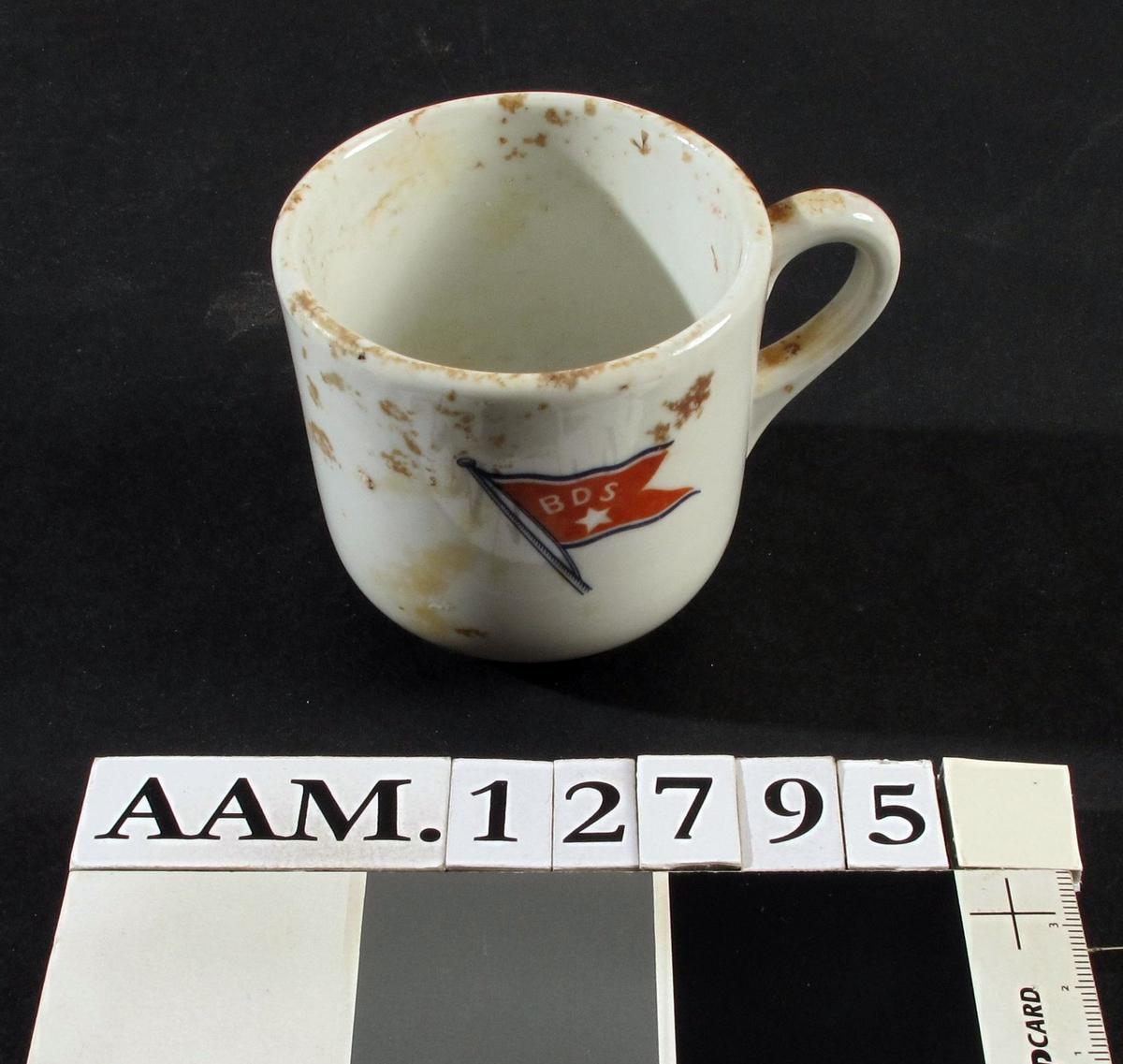 Kopp.  Porsgrunns porselenfabrikk, ca. 1930.  Antagelig fra D/S Neptun av Bergenske Dampskipsselskab, som gikk på grunn i Homborsund havn i 1941.  Båten var bygget i 1930.  Porselen.  Rettsidet kopp av tykt porselen med rund hank. Smal bunnring.  På siden BDS-flagg med stjerne i rødt.  Jernring i hanken for oppheng.  Samme som AAM.12796