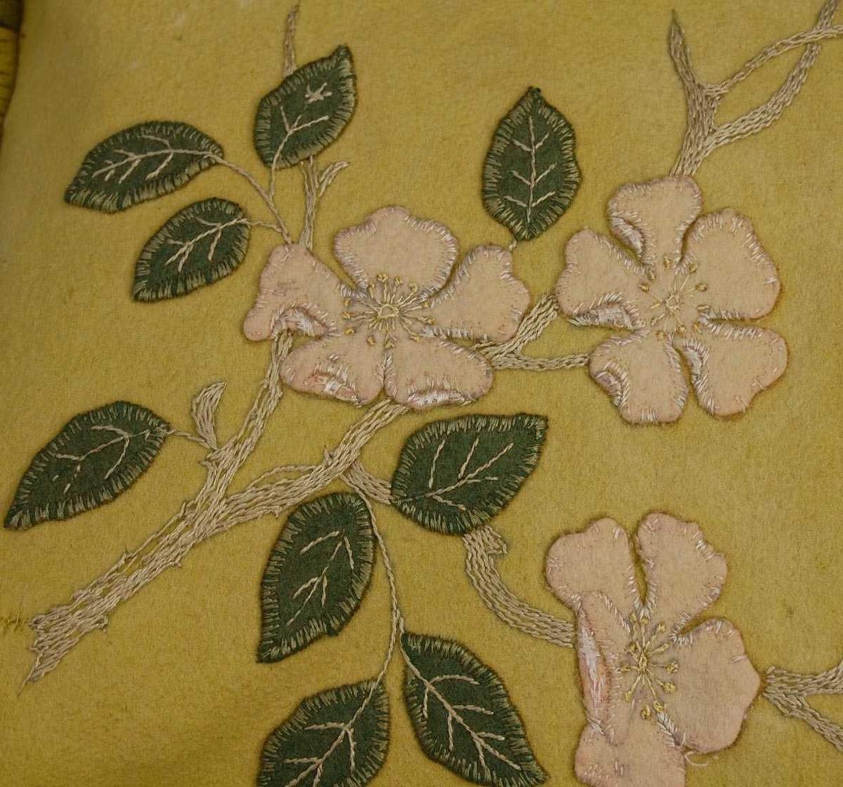 Pute med applikasjoner/blomsterbroderi. Forsiden av filt, med klipte løkker av filt til frynser. Baksiden av bomull? På baksiden er hull stoppet med kunststopping.