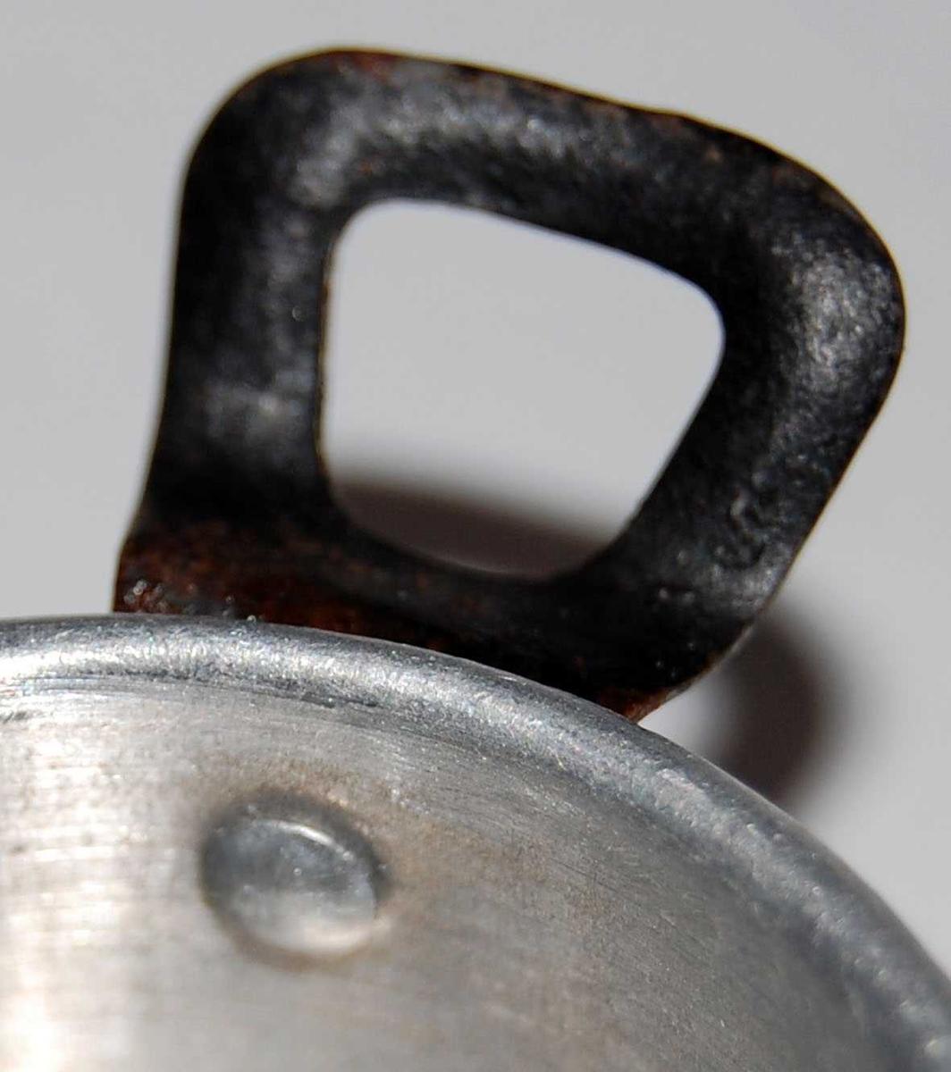 Dukkekjelesett i alumnium med påklinkete hanker i svartlakkert stål. A en kasserolle med lang hank. B og C gryter med ører. Grytene har falset kant.
