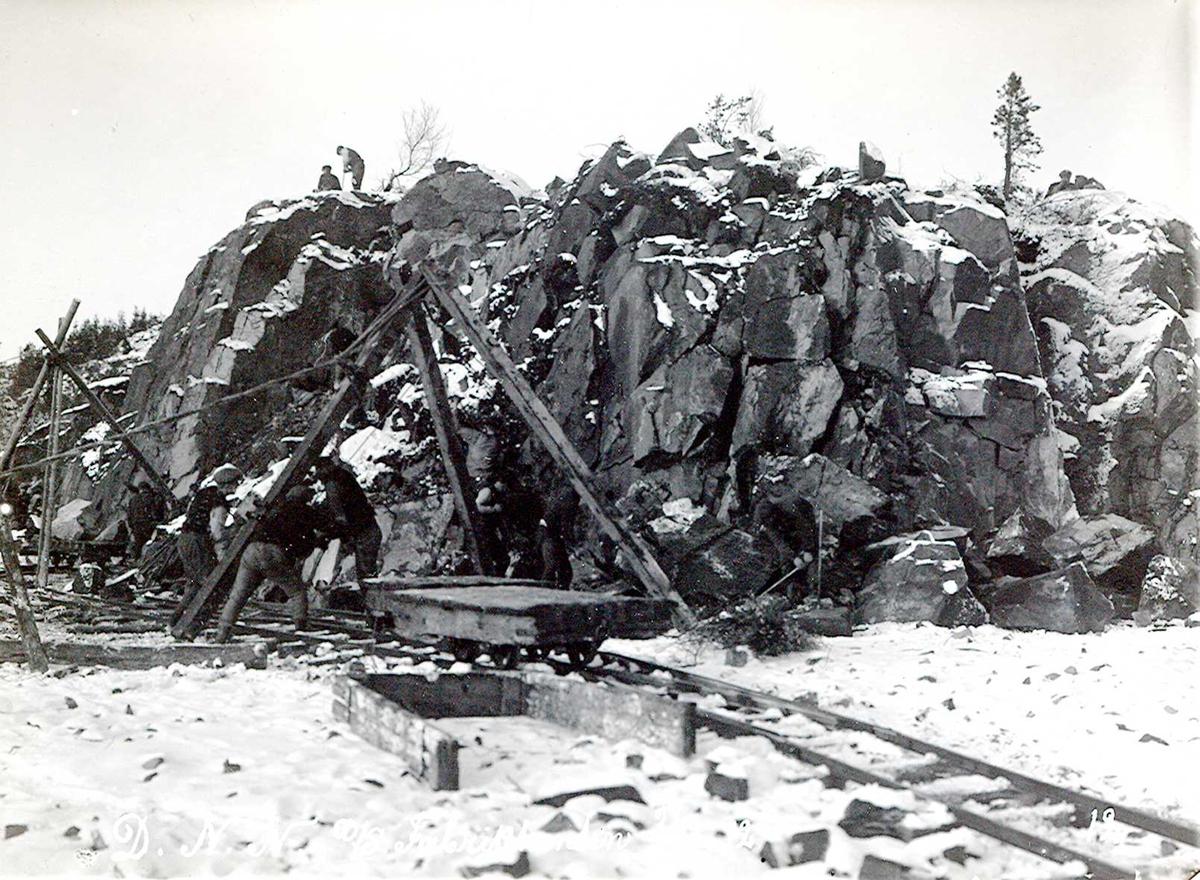 """""""1912"""" Nitriden. Utsprengning og planering av fabrikktomten. Heisanordning (stubbebryter) for løfting av steinblokker. Tralle på skinnegang. Løs karm, for påsetting på trallen, liggende på bakken. To mann holder på med minering på toppen av knausen."""