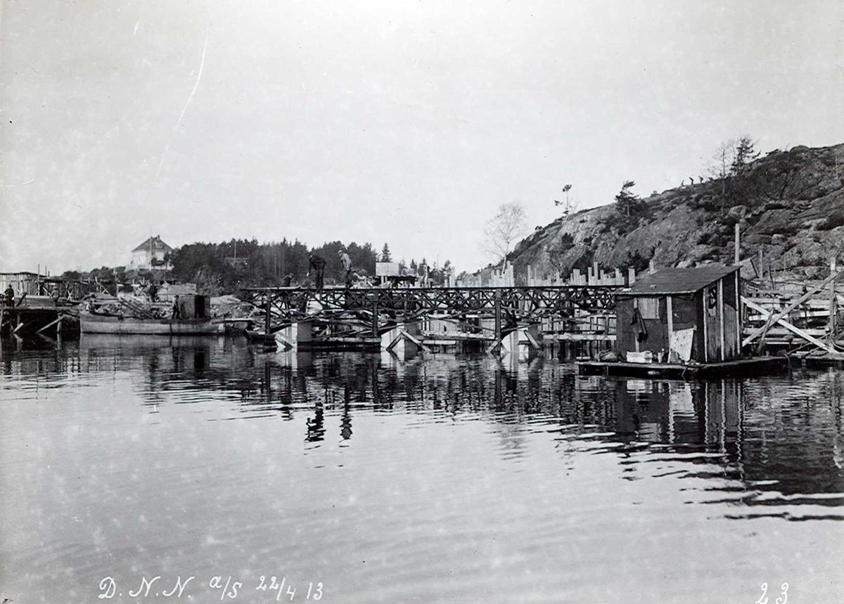 """""""22/04-1913"""" Nitriden. Bygging av kaianlegget i full gang. Jernkonstruksjoner. Forskalinger. Dykkerbåt. Smelteverkets første direktørbolig på høyden i det fjerne."""