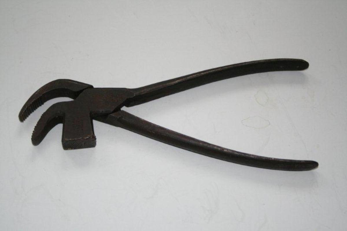 Kraftig buet nebb, riflet på innsiden av kjevene. Begge armer er noe bøyet. Mellom nebbet og den nedre armen er pinnetangen formet som en firkantet hammer med riflet bane.