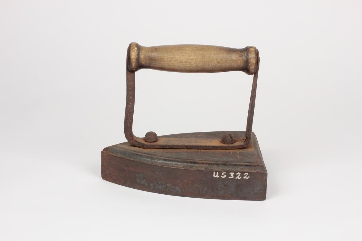 Form: Svakt oppbøyde kanter. Trekantformet. En av stengene i U-formen smalere enn den andre. Varmes på ovn. Håndtakets øverste del er et dreid umalt trestykke, klinket på det U-formede jernstykket som er festet med to rundhodete skruer. Jernet må oppvarmes på ovn. Tidl. reg.: Pressjern - skredder. Johs. Fløtten. Tidl. reg. nr. 63